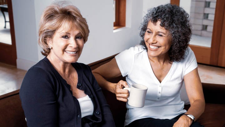 A pair of mature ladies share some gossip over a cup of coffee.