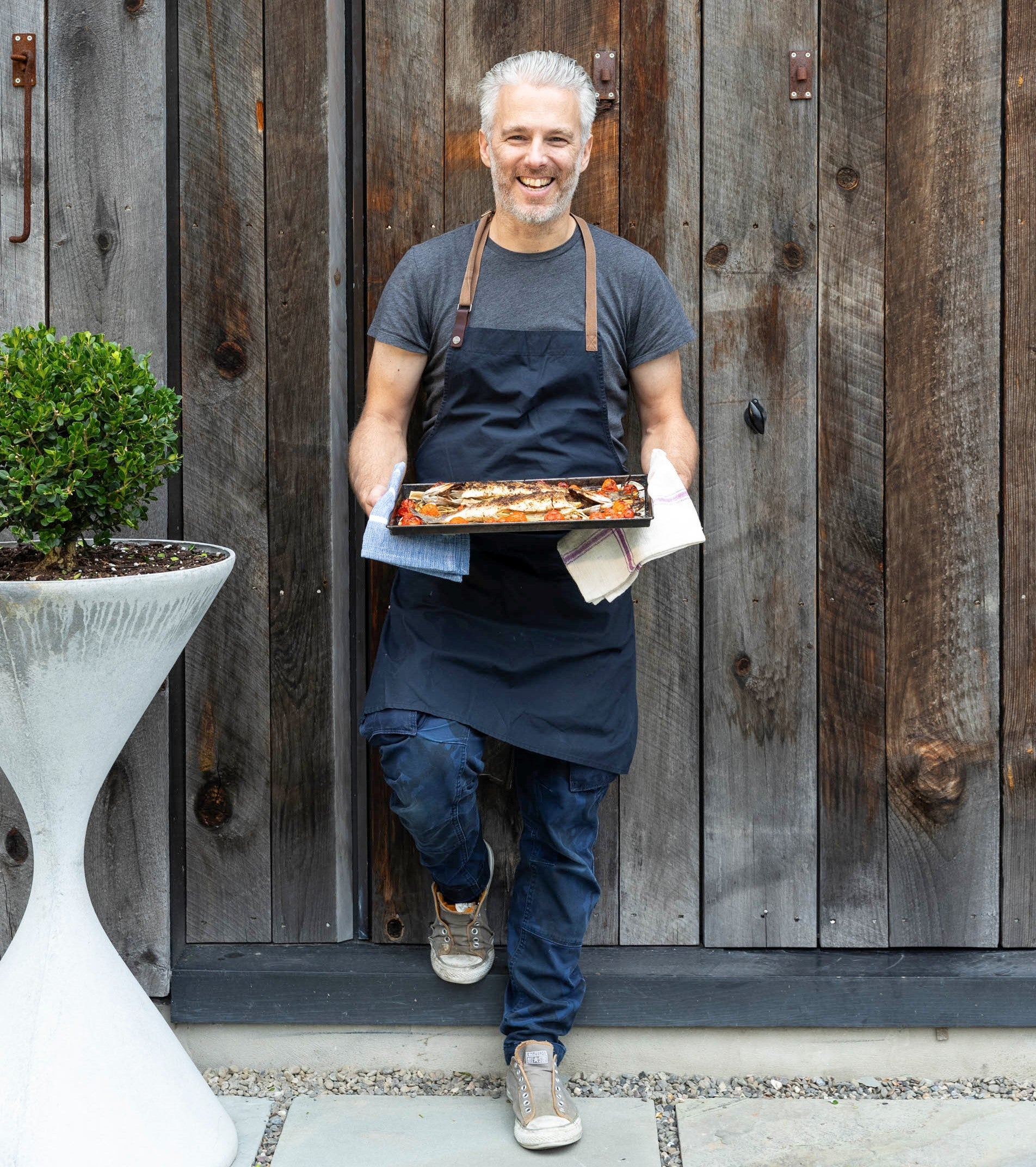 Israeli chef and spice master Lior Lev Sercarz is holding a tray of food and smiling